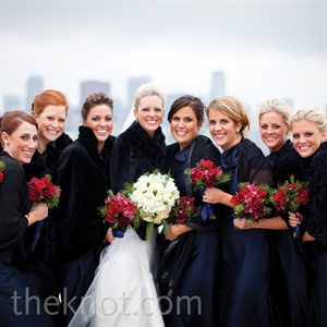 Katies bridesmaids wore formal navy floor-length gowns topped off with black shawls or faux-fur jackets.