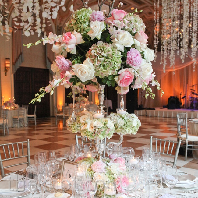 Blush-pink peonies, roses and orchids made up the high and low centerpieces at the reception. A trio of silver candleholders completed the look.