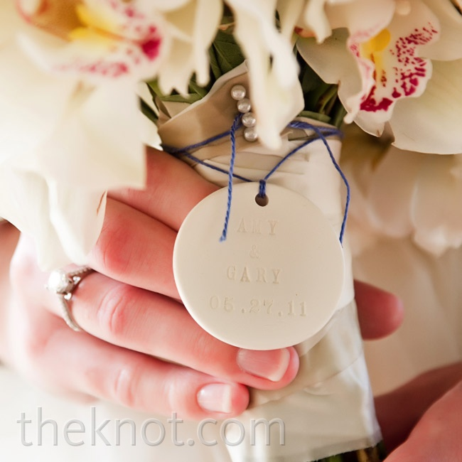 A large porcelain charm stamped with the couple's names and wedding date dangled from the handle of Amy's white orchids.