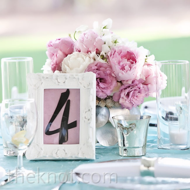 Fluffy pink and white peonies, lisianthus, and sweet peas had the feminine feel Amy was aiming for, while capiz-shell-covered vases brought in a nod to the oceanside location.