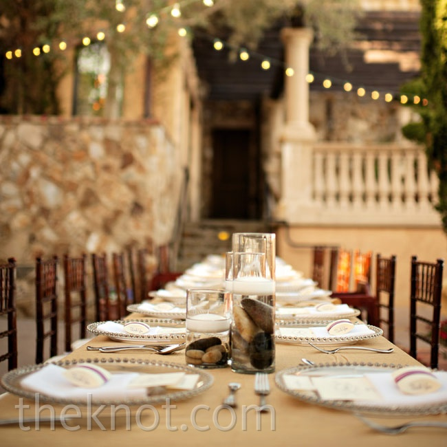 Long banquet tables topped with cylinder vases full of river rocks and floating candles had an effortless feel.