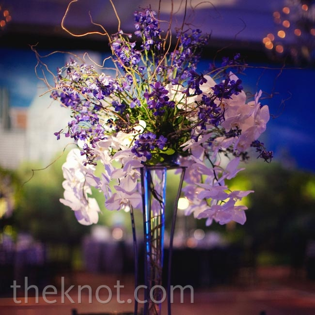 Orchids and branches cascading from modern metal-and-glass vases matched the colors in the reception backdrop.