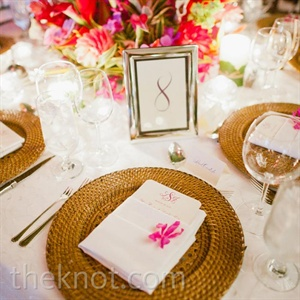 Wicker chargers and exotic floral centerpieces brought in the tropical theme, while silver framed table numbers reinforced the traditional side of the couple's style.