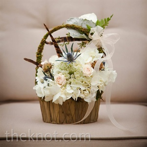 The flower girl carried a moss basket full of white blooms down the aisle.