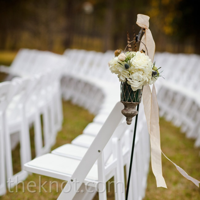 Flowers tucked inside vintage lanterns hung from shepherd's hooks along the ceremony aisle.