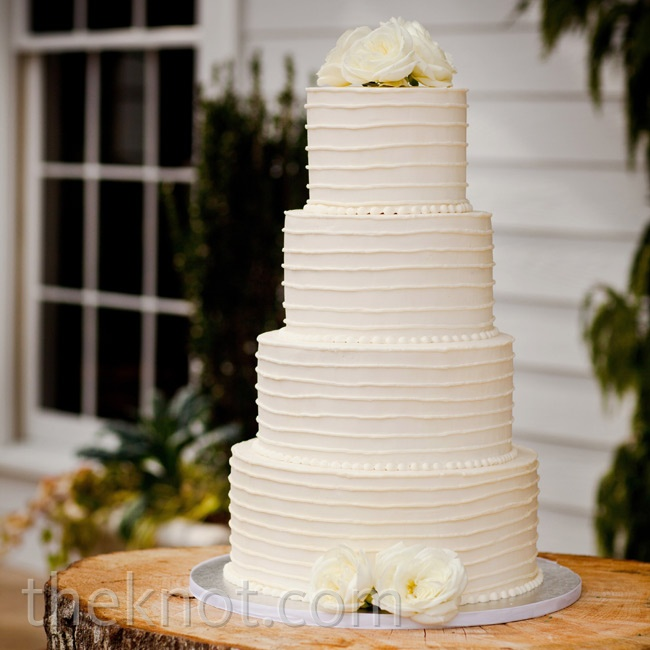 The all-white cake got just a few simple touches: combed buttercream frosting and a handful of fresh white flowers.