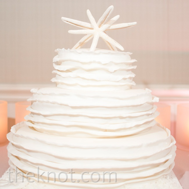 Instead of traditional bride and groom figurines, two starfish topped the white ruffled wedding cake.