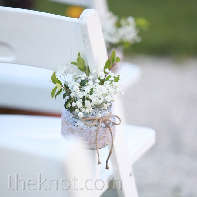 Small Mason jars of white flowers tied with twine highlighted the aisle in a simple understated way.