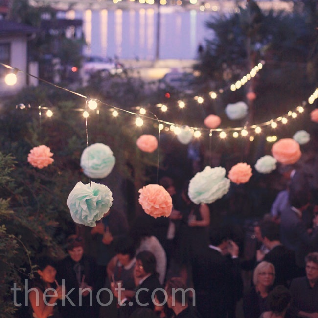 Colorful paper pom-poms and stringed lights hung over the dance floor.
