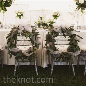 The newlyweds' chairs were decorated with leafy wreaths wrapped in tulle ribbon.