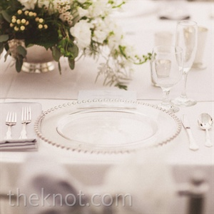 Glass beaded chargers and silver napkins gave the tables a crisp look.