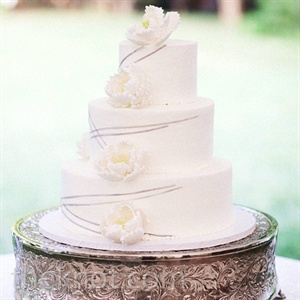 The white three-tiered cake was decorated with sugar peonies and silver string ribbon.