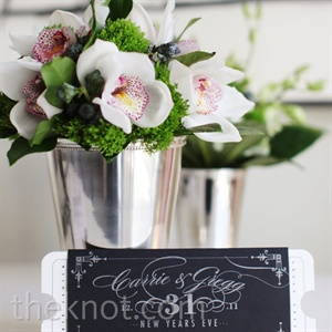 Silver pots with white orchids and green topped the reception tables.