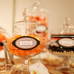 Orange candies in glass jars were marked with vintage-style labels and displayed as table favors.
