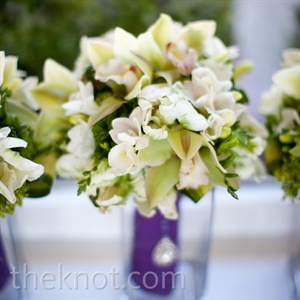 White-and-green bouquets were wrapped in rich purple ribbon.
