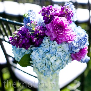 A mixture of cool blue and warmer purple flowers lined the ceremony aisles.