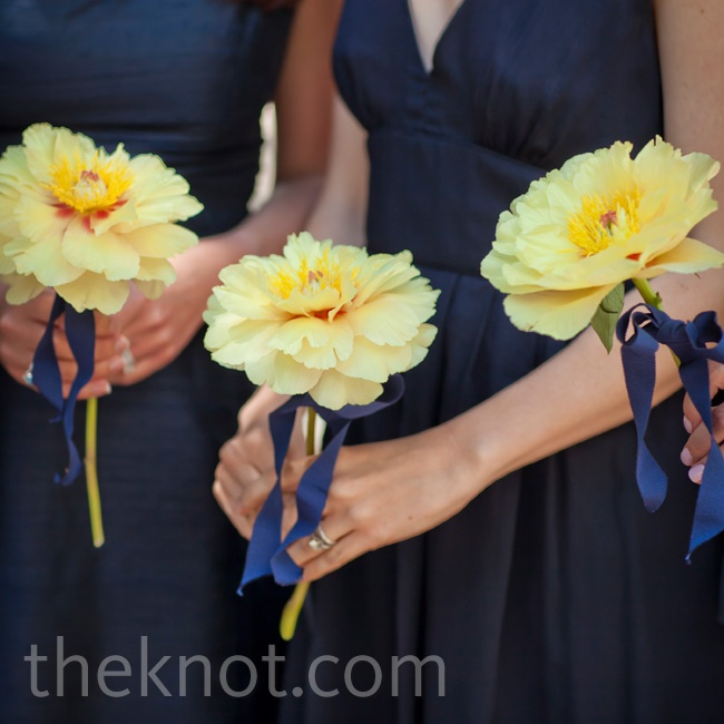 The girls held single yellow peony blooms.