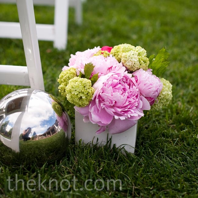 Setting a modern tone early, white square vases and silver spheres lined the ceremony aisle.