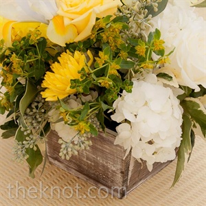 Wild greenery with yellow and white blooms seemed to spill out from weathered wooden boxes.