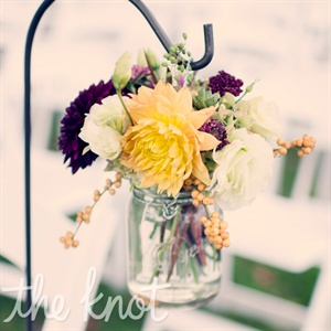 Naturally arranged flowers in Mason jars hung from shepherd's hooks along the ceremony aisle.