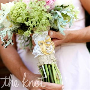 Burlap and lace wraps held together the lush bouquets and were accented with vintage brooches.