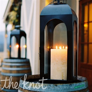 Candlelit lanterns were perched atop rugged wine barrels, flanking the entrance to the venue.