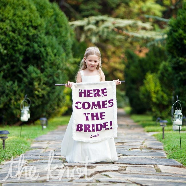 The couple took a playful approach to the procession and had Samantha's cousin Cassandra carry a banner down the aisle.
