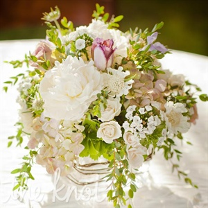 Overflowing arrangements of hydrangeas, peonies, roses, and greenery added a wild feel to the tables.