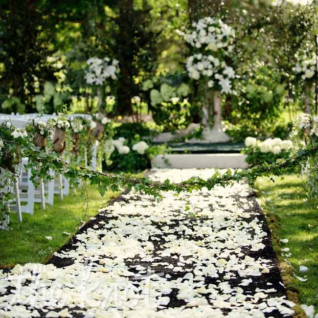 To protect the wedding party from the wet ground, a wooden aisle beautified with black carpet and rose petals was laid on the grass.