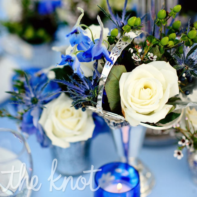Silver mint julep cups and trophy cups filled with blue flowers topped some of the reception tables.