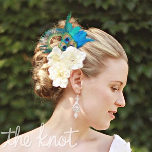 A peacock-feather clip and white silk flowers were tucked into Jessica's curly updo.