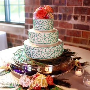 Geometric teal lines with a bright topper made of fresh flowers gave the cake a dose of the wedding colors.