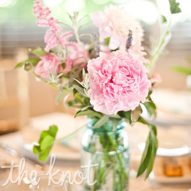 Pink peonies and other blooms filled aqua-tinted Mason jars on the tables.