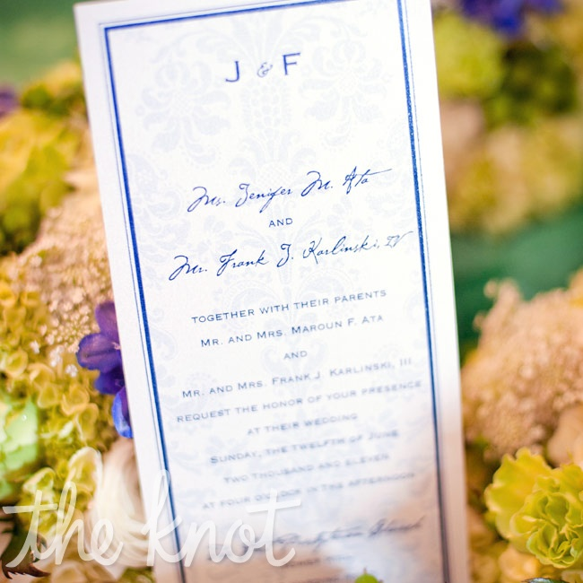 Tea-length invites with a navy-damask background and navy print reminded the couple of the wallpaper design at their venue.