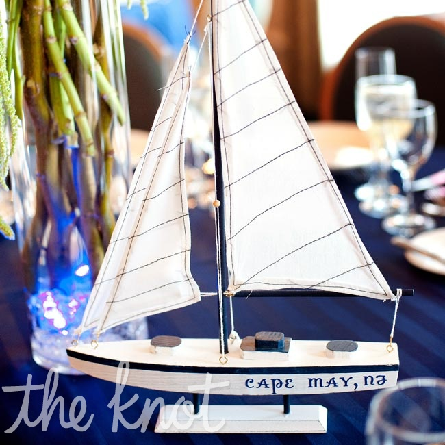 Instead of numbers, the couple used harbor names to identify each table and displayed them on the base of mini sailboats.