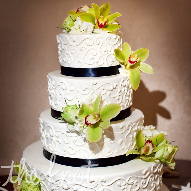 Fresh orchids popped on the white cake, which was also decorated with navy ribbon and an elegant scroll design.