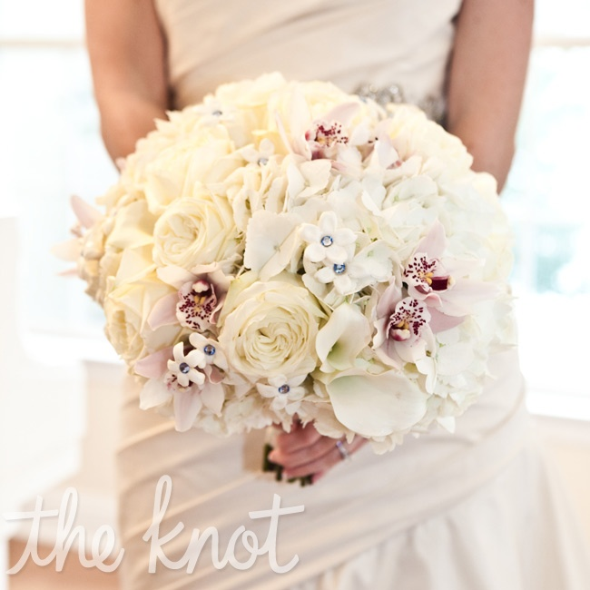 Ivory calla lilies, cymbidium orchids, and stephanotis blooms embellished with blue crystals made up Erin's lush bouquet.
