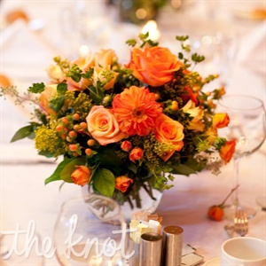 Roses, goldenrods, and dahlias in shades of peach, orange, and yellow decorated the tables at the reception.