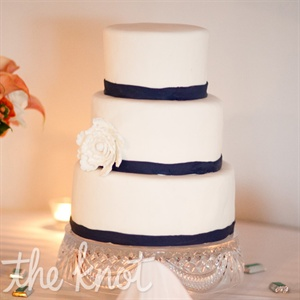 The three-tiered white cake was wrapped with a navy ribbon and accented with sugar flowers.