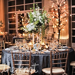 Cascading arrangements of white flowers, manzanita branches and candles topped the reception tables.