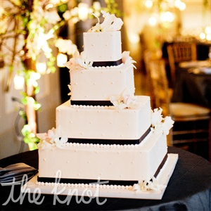 The four-tiered white cake was decorated with fresh flowers and wrapped with black ribbon.