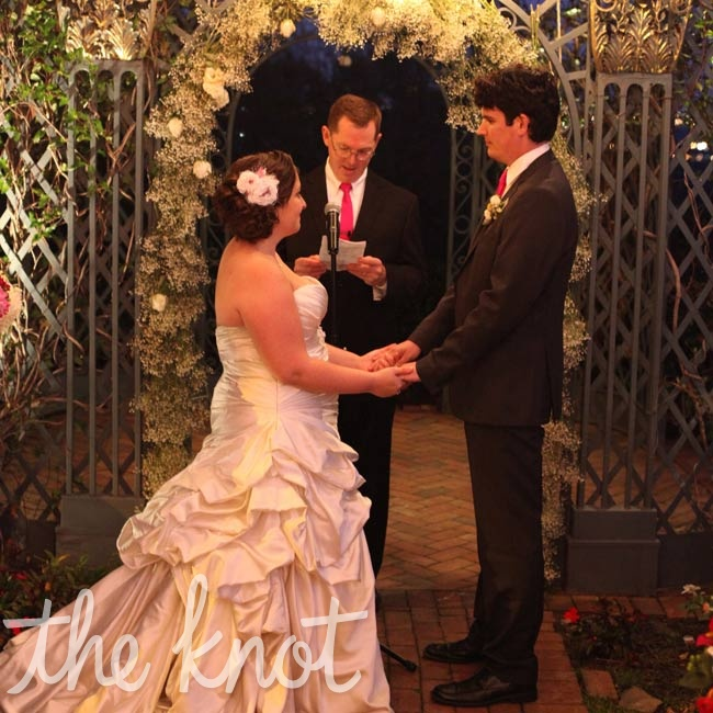 Sarah and Clint wed outside under a flower- and lantern-decorated arbor.