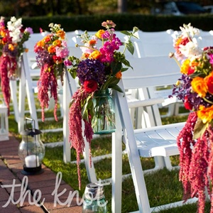 Lanterns lined the ceremony aisle, along with hanging Mason jars filled with fresh pink and orange flowers.