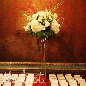 A tall vase filled with white roses and hydrangeas served as the focal point of the escort card table.