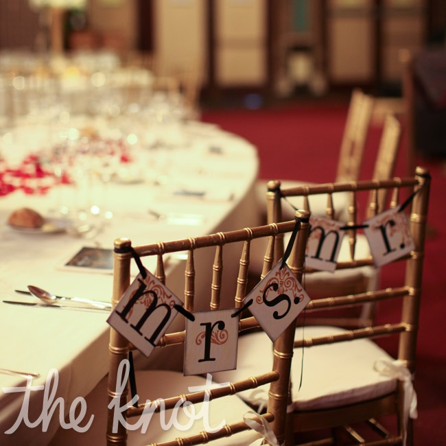 "Embellished ""Mrs."" and ""Mr."" signs hung from the newlyweds' reception seats."