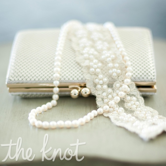 Lara accessorized with an elegant pearl necklace and a chic evening bag.