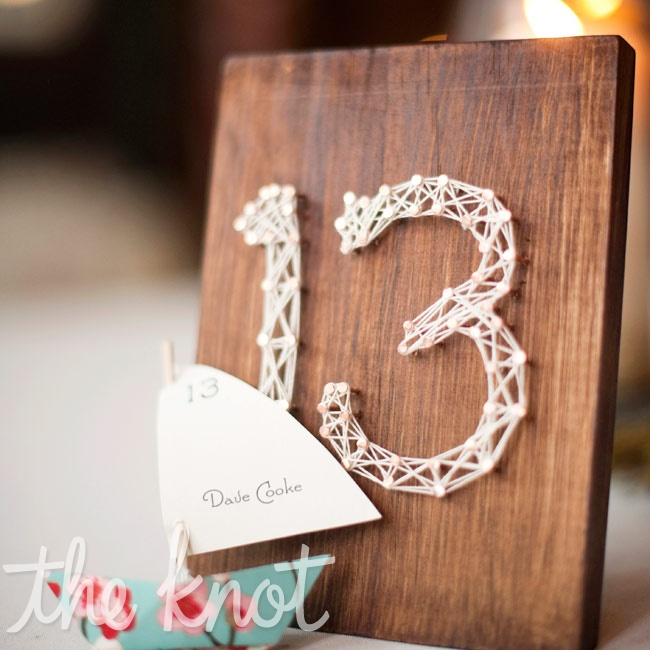 White string art on stained pieces of wood served as unique table numbers.
