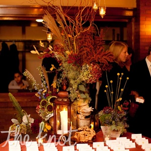 A table outside the main reception room displayed lanterns, a mix of rustic floral arrangements and the escort cards.