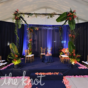 Lots of colorful tropical flowers, foliage, and navy draping framed the couple's elaborate mandap.