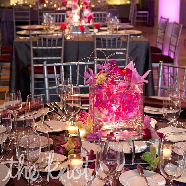A sculptural arrangement of wire and pink orchids in a square glass container was one of the reception's three modern centerpiece styles.